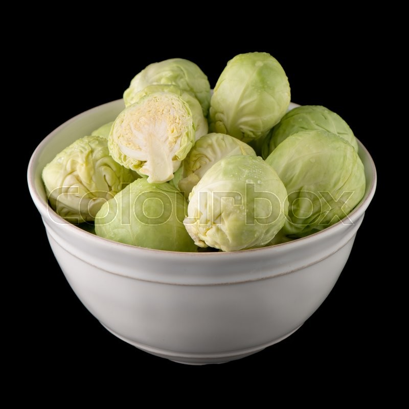 Stock image of 'Fresh brussels sprouts on white ceramic bowl isolated on black background.'