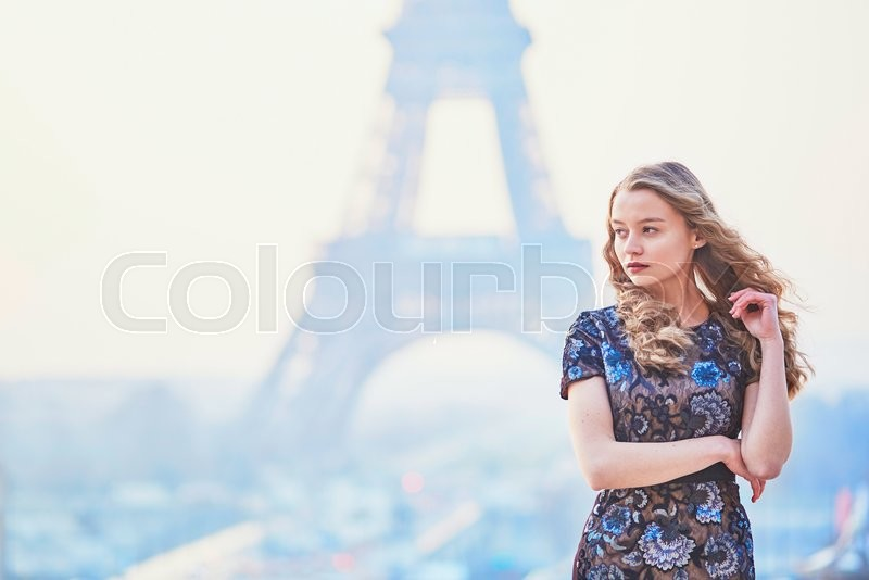 Stock image of 'Beautiful elegant Parisian woman near the Eiffel tower at early morning'