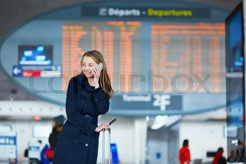 Stock image of 'Young woman in international airport near the flight information board, using her mobile phone'