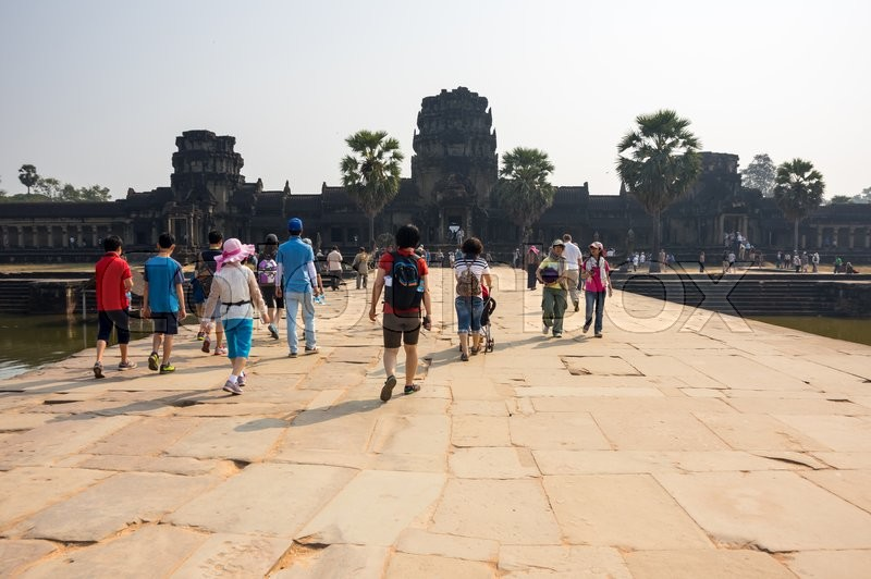 Editorial image of 'ANGKOR WAT, CAMBODIA - JANUARY 27, 2015: Tourists walking to the entrace of Angkor Wat temple in Cambodia. Angkor Wat is the largest Hindu temple complex and religious monument in the world'