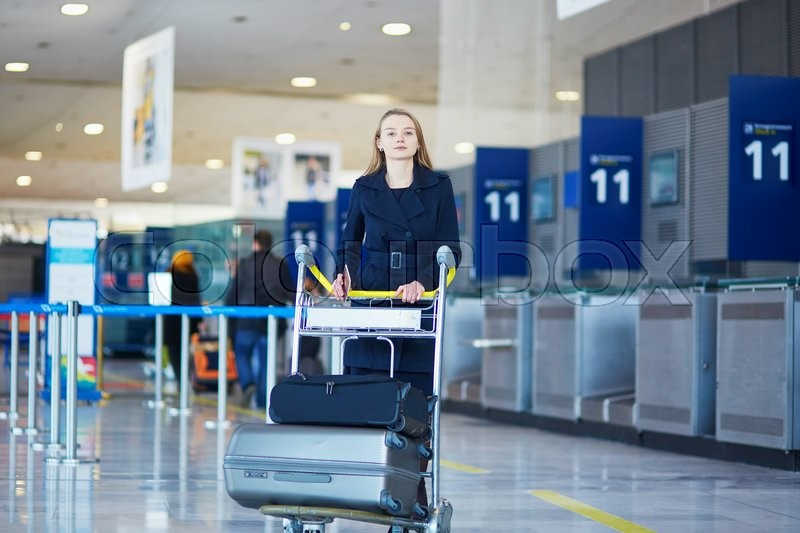 Stock image of 'Young woman in international airport, with luggage trolley'