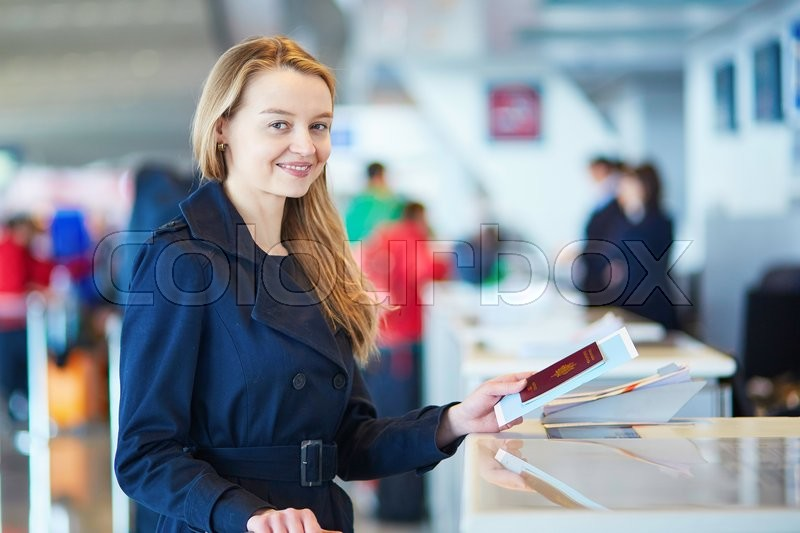 Stock image of 'Young woman in international airport at check-in counter, giving her passport to an officer and waiting for her boarding pass'