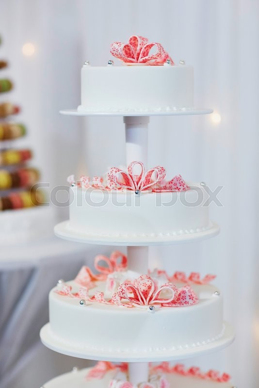 Stock image of 'White wedding cake decorated with pink sugar flowers'