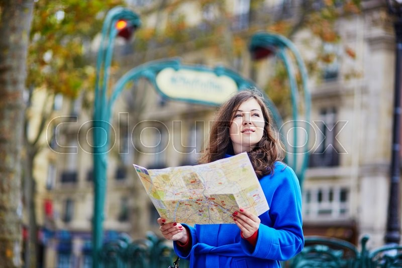 Stock image of 'Beautiful young tourist in Paris, using map near metro station'