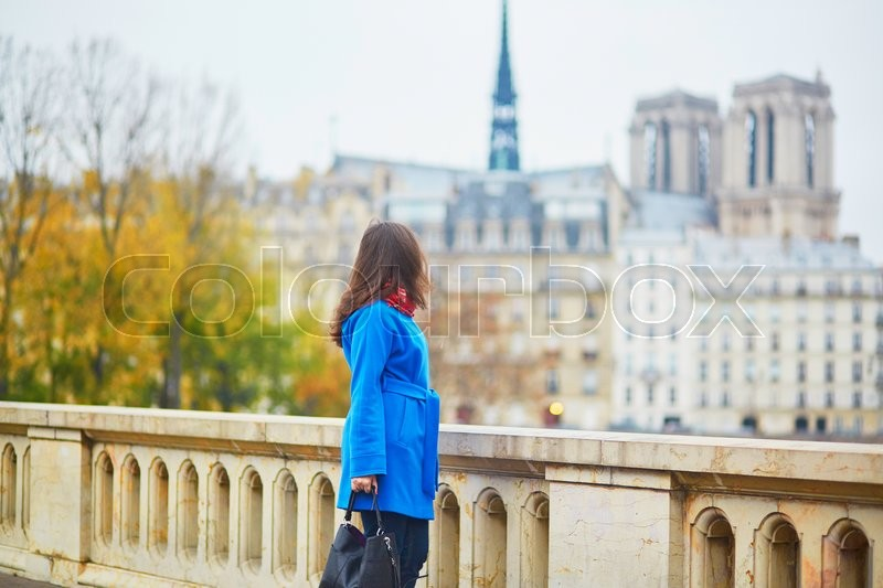 Stock image of 'Beautiful young tourist in Paris, walking near Notre-Dame cathedral'