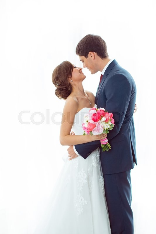 Stock image of 'Wedding couple in love. Beautiful bride in white dress with brides bouquet and handsome groom in blue suite standing and embracing each other indoors at home, white bright isolated background'