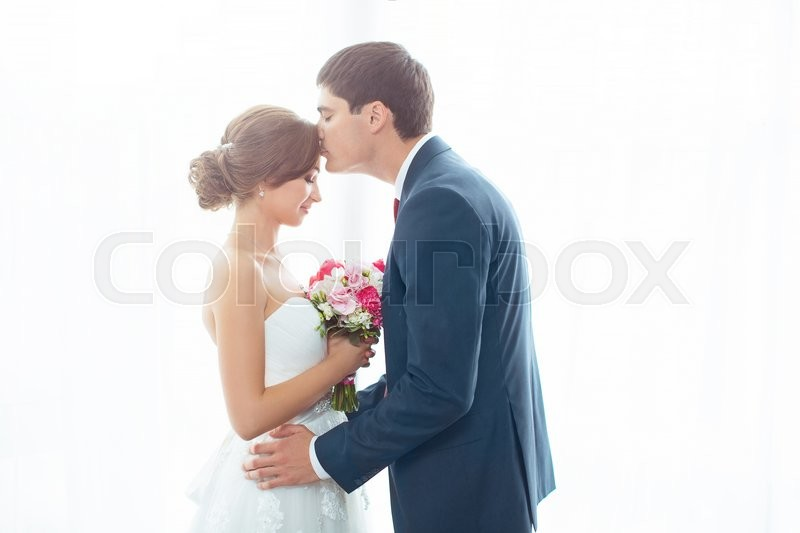 Stock image of 'Wedding couple in love. Beautiful bride in white dress with brides bouquet and handsome groom in blue suite standing and embracing each other indoors at home, white bright isolated background. Husband kissing his wife'