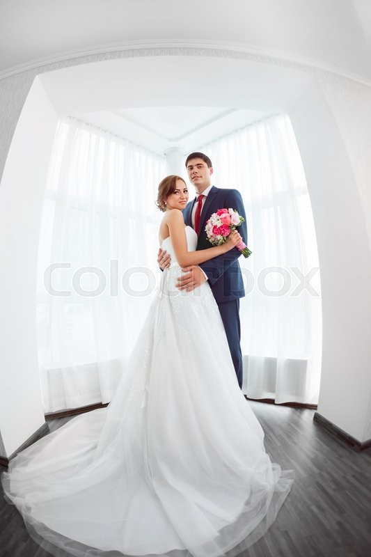 Stock image of 'Wedding couple in love. Beautiful bride in white dress with brides bouquet and handsome groom in blue suite standing and embracing each other and lookin at camera indoors at home, white bright room with big window High key, made on fisheye lens photo.'