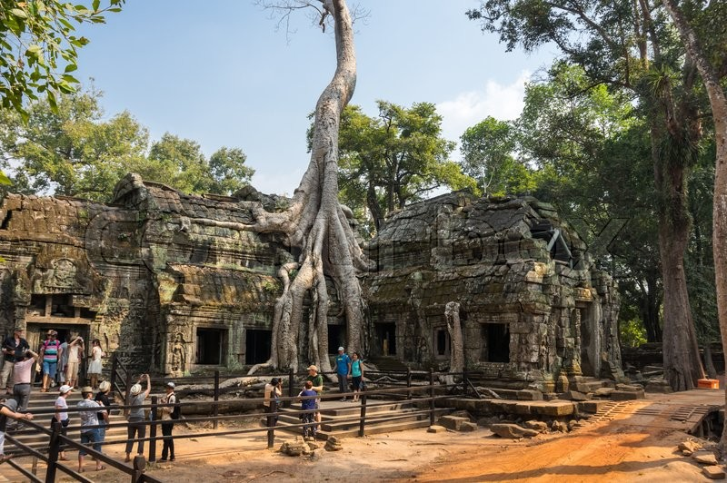 Editorial image of 'ANGKOR WAT, CAMBODIA - JANUARY 27, 2015: Unidentified tourists at Ta Prohm temple in Angkor Wat. Angkor Wat is the largest Hindu temple complex and religious monument in the world'