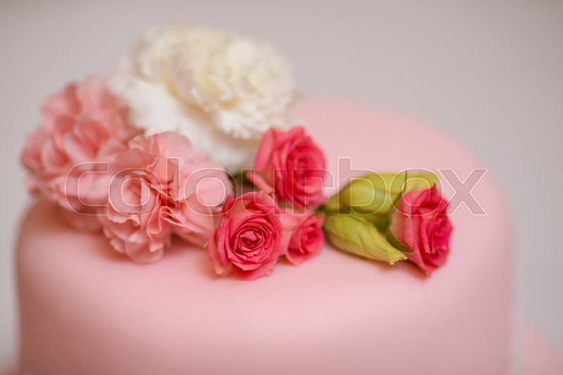 Stock image of 'Close-up pink wedding cake with roses against  copy space background'