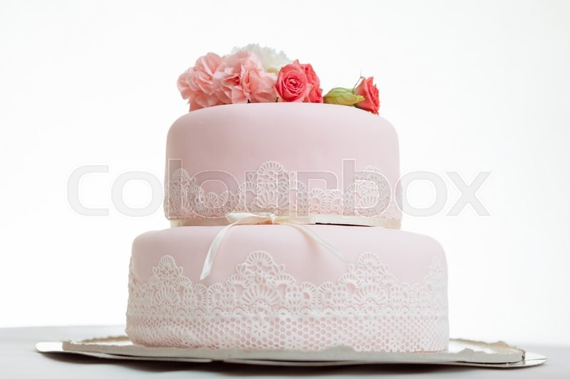 Stock image of 'Pink wedding cake with roses against  white isolated background'