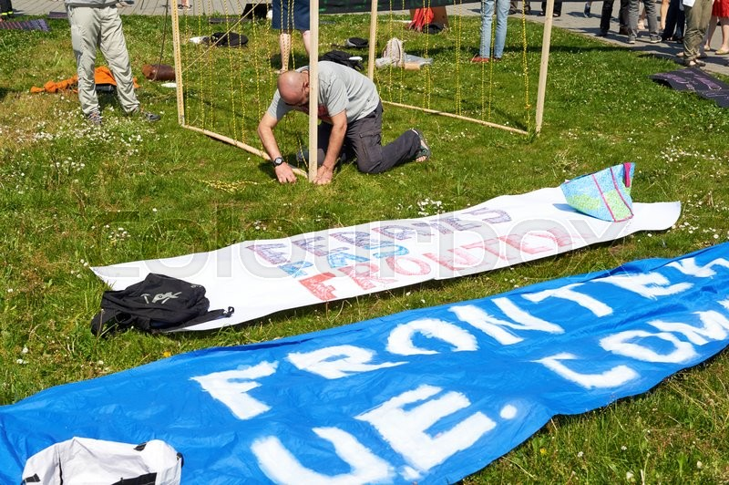 Editorial image of 'STRASBOURG, FRANCE -MAy 8, 2016: Open Doors day, Closed doors at borders - protest in front of the European Parliament during EU migrant policy - man preparing placards'