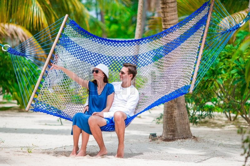 Stock image of 'Happy couple on tropical vacation relaxing in hammock'