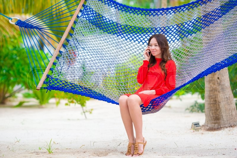 Stock image of 'Beautiful woman relaxing at hammock on tropical beach'