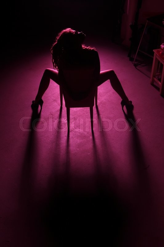 Stock image of 'Beautiful girl on a chair in the violet filter'