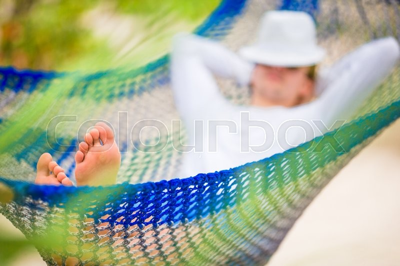 Stock image of 'Lazy time. Man in hat in a hammock on a summer day'