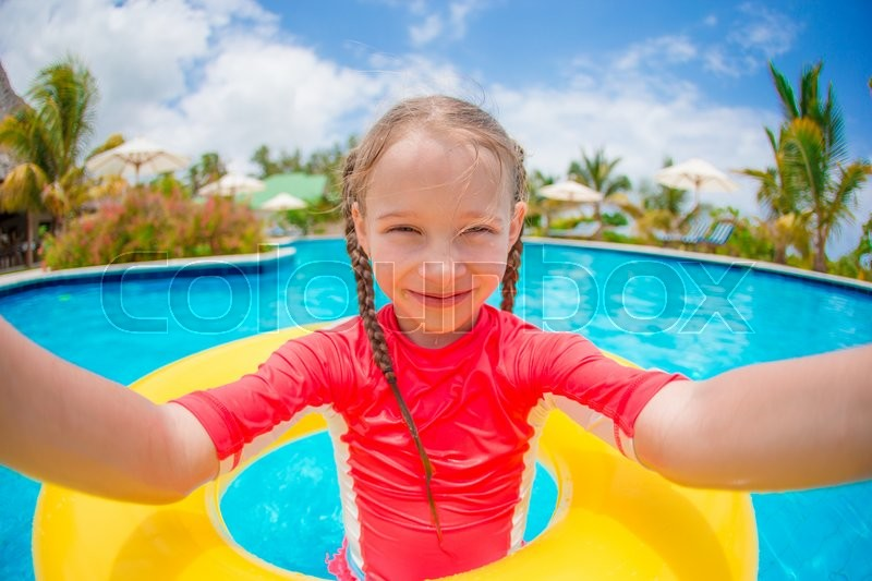 Stock image of 'Little girl making selfie at inflatable rubber ring in swimming pool'