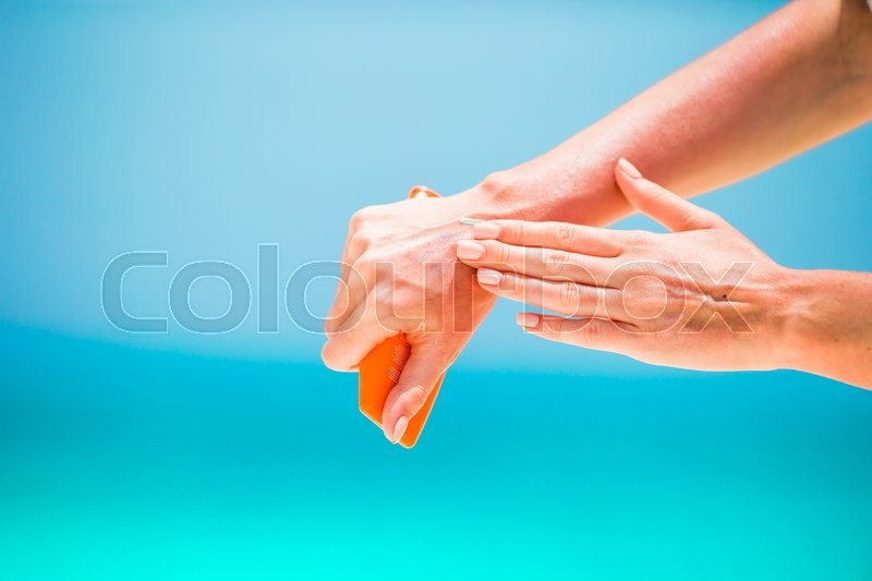 Stock image of 'Woman hands putting sunscreen from a suncream bottle background the sea'