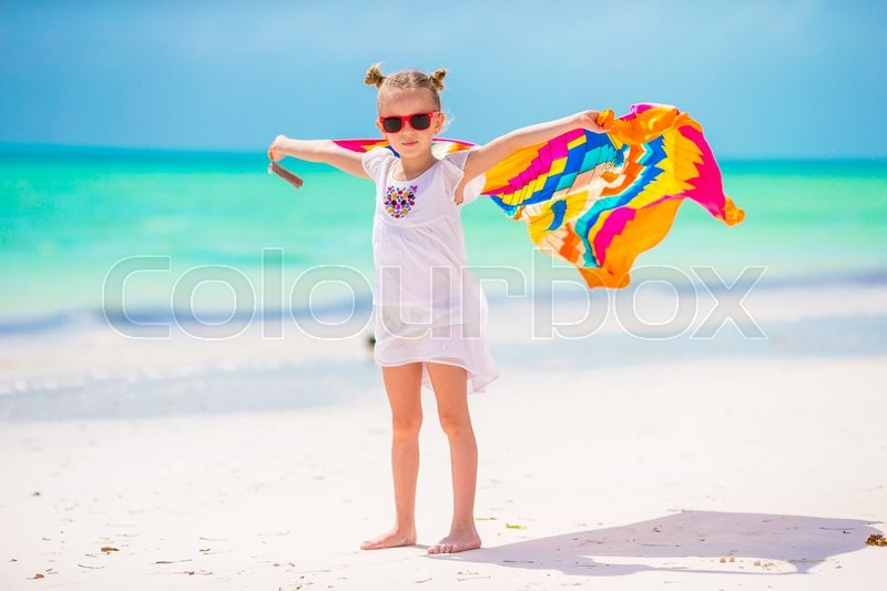 Stock image of 'Little adorable girl with beach towel during tropical vacation'