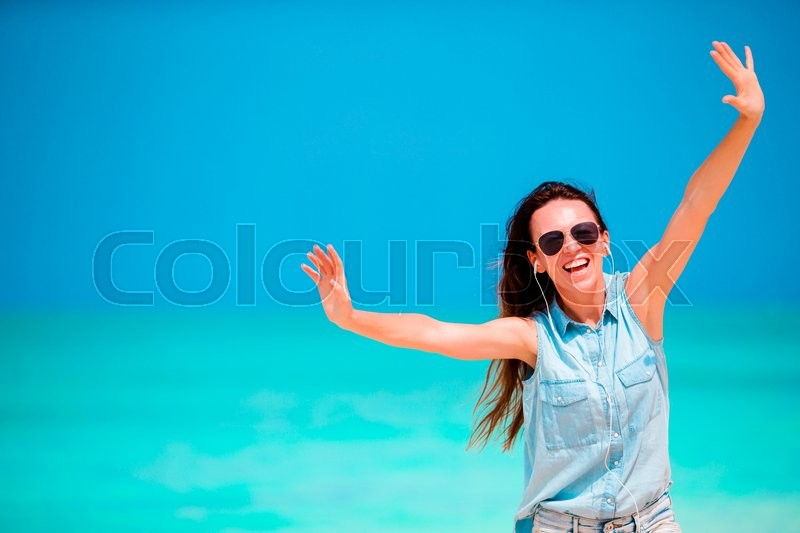 Stock image of 'Young beautiful woman listening to music on white  beach'