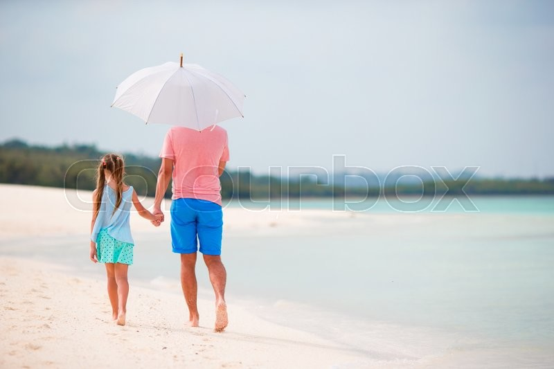 Stock image of 'Father and little girl with umbrella hiding from sun at beach'