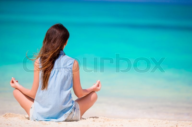 Stock image of 'Happy relaxed young woman practicing yoga outdoors at white beach'