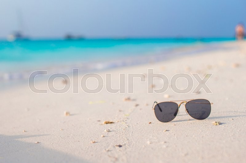 Stock image of 'Close up of colorful blue sunglasses on tropical beach'