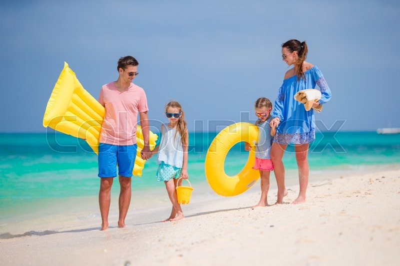Stock image of 'Happy beautiful family on white beach with air mattresses'