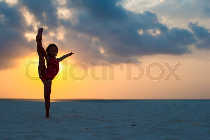 Stock image of 'Silhouette of adorable active little girl on white beach at sunset'