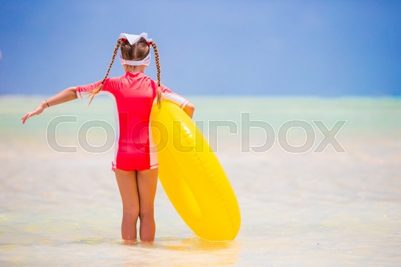 Stock image of 'Adorable girl with inflatable rubber circle on white beach'