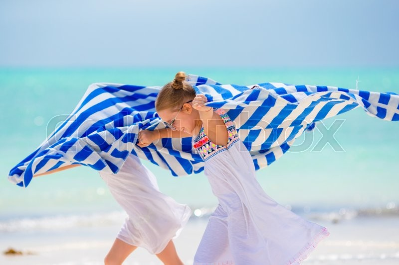 Stock image of 'Little girls having fun running with towels on tropical beach with white sand and turquoise ocean water'