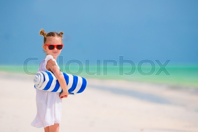 Stock image of 'Little girl with towels on white beach vacation'
