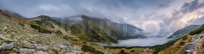 Stock image of 'Mountains Landscape with Fog in Ziarska Valley. Rocks in Foreground.'