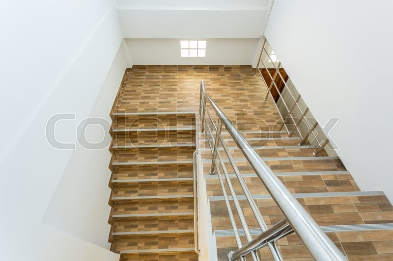 Stock image of 'staircase in residential house with stainless steel banister, ceramic floor tiles wood pattern'