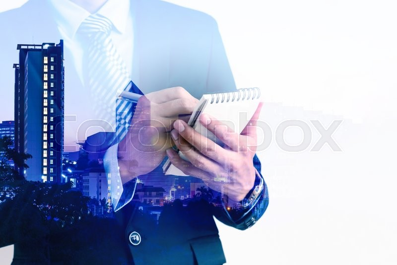 Stock image of 'Double exposure of businessman writing on packet notebook with city background.'