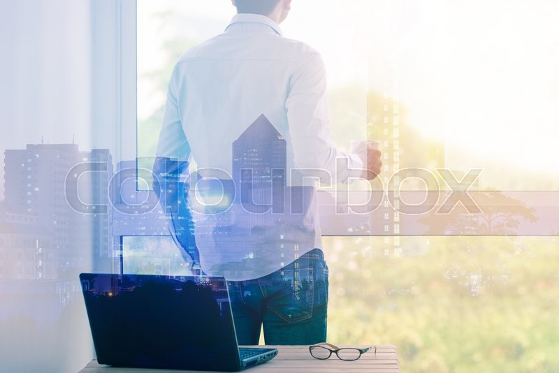 Stock image of 'Double exposure of businessman relaxing with hot coffee by the window on cityscape.'