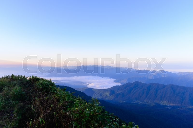 Stock image of 'Sunrise and mist with mountain in Chiang Mai, Thailand.'
