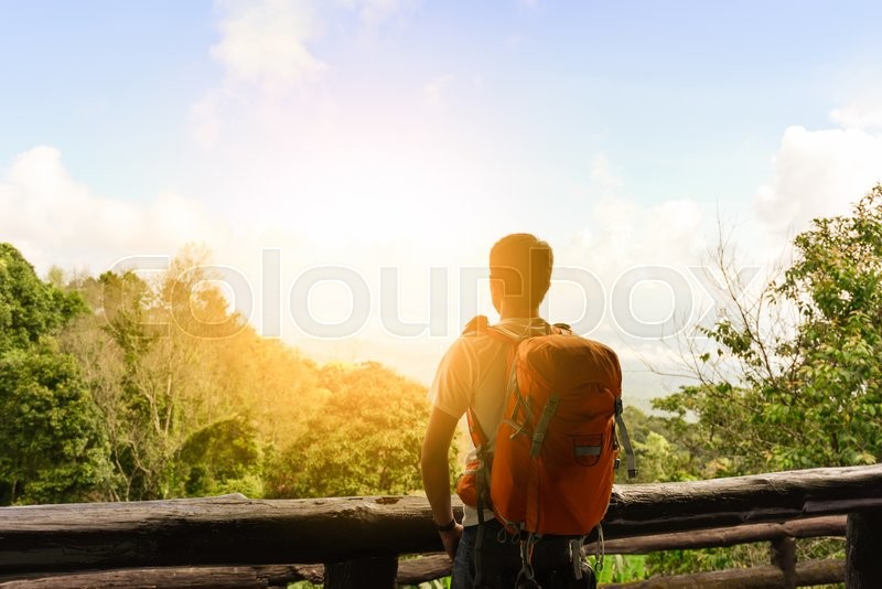 Stock image of 'Man hiker with orange backpack looking view of mountain.\\ '