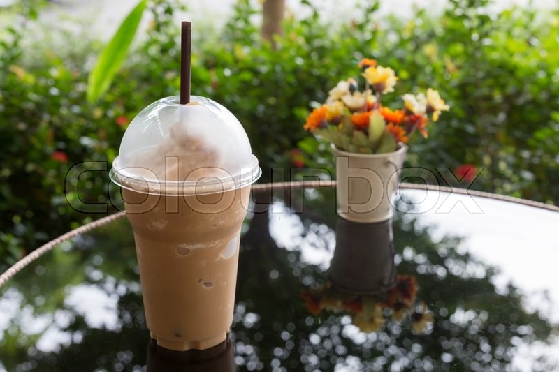 Stock image of 'cold ice coffee drink put on glass table in the garden'