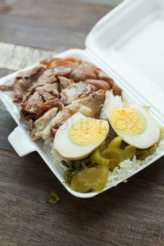 Stock image of 'Thai food, lunch box stewed pork leg on rice with boiled egg'