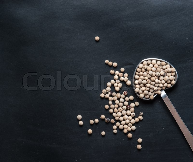 Stock image of 'White pepper seeds in spoon on a black slate'