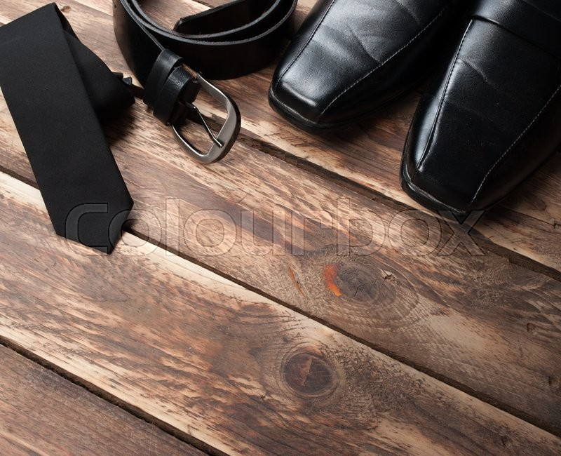 Stock image of 'Man's style accessories,tie, shoes and a belt on wooden background'