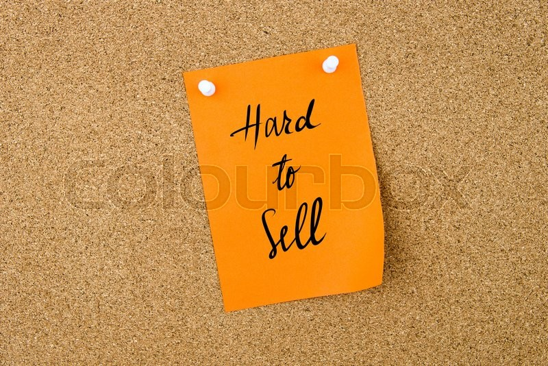 Stock image of 'Hard To Sell written on orange paper note pinned on cork board with white thumbtacks, copy space available'