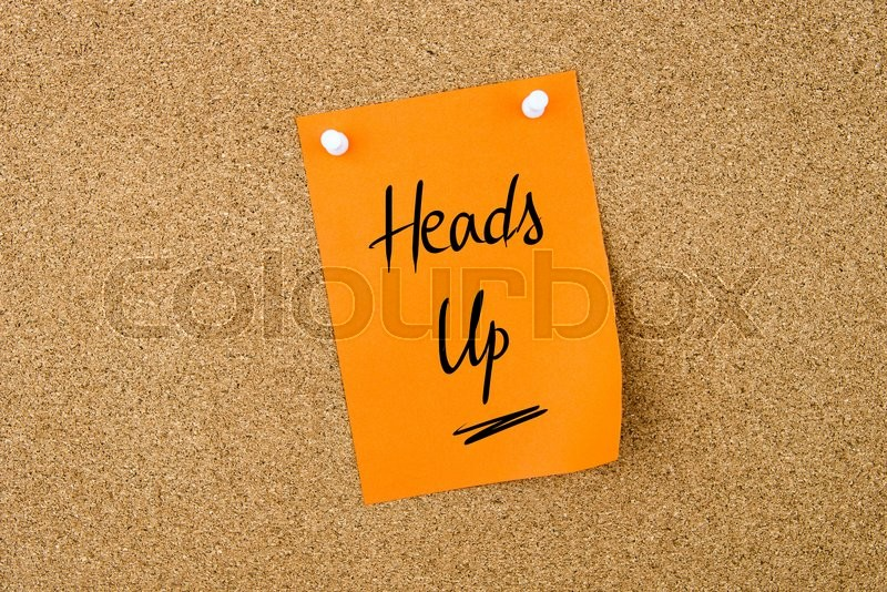 Stock image of 'Heads Up written on orange paper note pinned on cork board with white thumbtacks, copy space available'