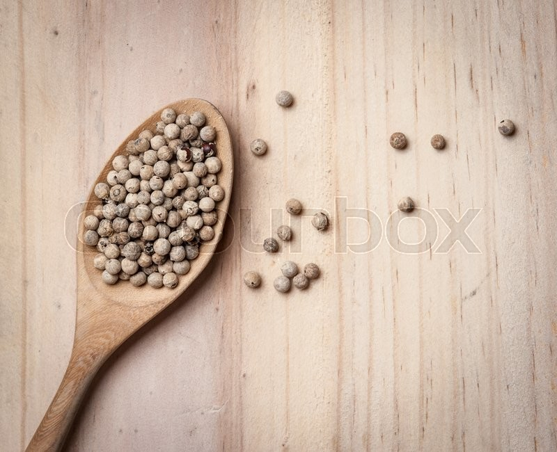 Stock image of 'White pepper seeds in spoon on the wood table'