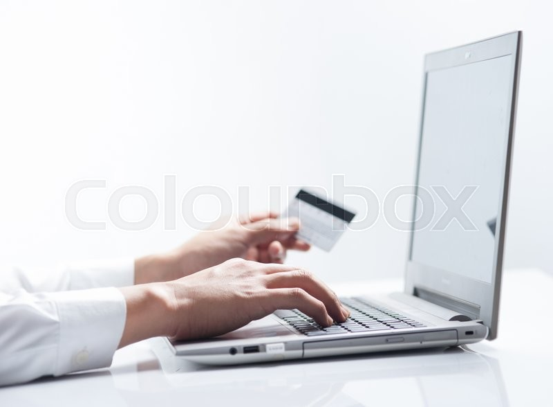 Stock image of 'Man with credit card using a laptop computer for internet shopping'