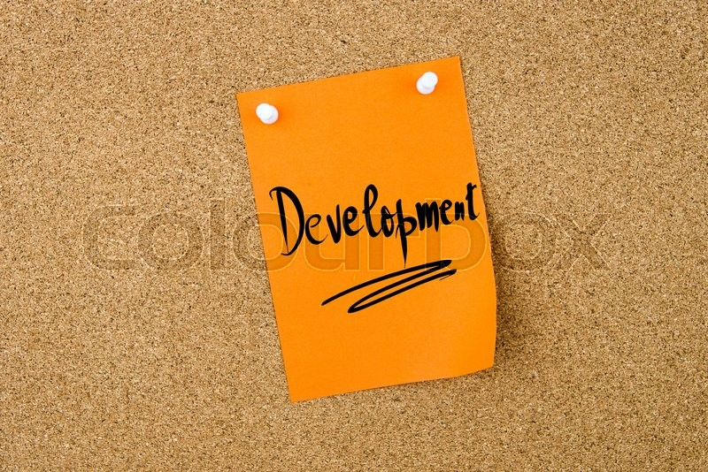 Stock image of 'Development written on orange paper note pinned on cork board with white thumbtacks, copy space available'