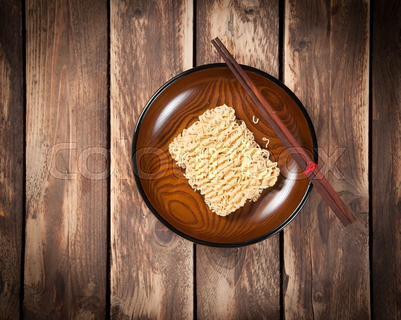 Stock image of 'Instant noodles in bowl on wooden,Top view'