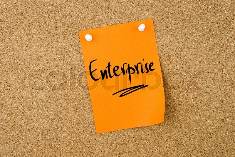 Stock image of 'Enterprise written on orange paper note pinned on cork board with white thumbtacks, copy space available'