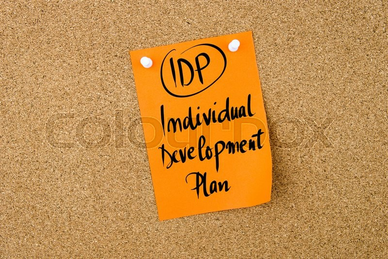 Stock image of 'Business Acronym IDP Individual Development Plan written on  yellow paper note pinned on cork board with white thumbtack, copy space available'
